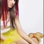 Девушка в жёлтой юбке и белом топике сидит на полу и держит в руках блестящие шары