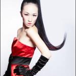 Девушка стоит в красном платье боком, рука на бедре