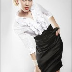 Девушка в черной юбке до колен и белой блузке стоит, наклонившись и оперевшись на колено
